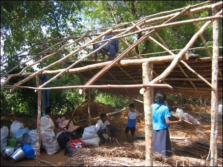 People putting up cooler shelters in Thampattai using cadjan leaves.