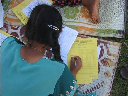 Officers of the Tamils Rehabilitation Organisation filling forms in Mandaanai welfare camp.