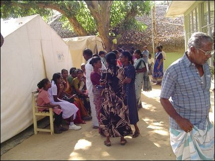 Patients waiting outside in the shade to gain entrance to the hospital. Temporary tents provide additional room for the new influx of patients after the tsunami.