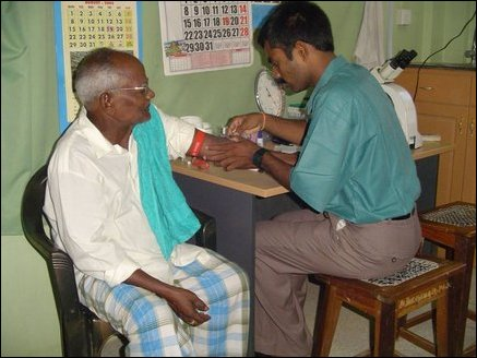 Locally trained lab technician prepares to get blood sample from a patient in a well equiped laboratory.