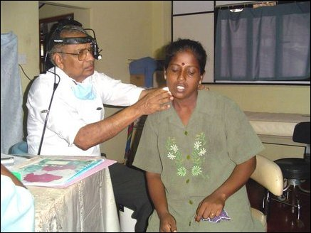 Dr Robert Benjamin, an ENT surgeon from New Zealand examining a patient in Ponnambalam Memorial Hospital.