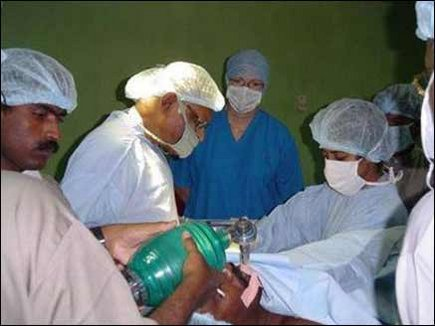 Dr. Charles Vivekanandan, a Plastic Surgeon from UK, performing surgery on a male patient.