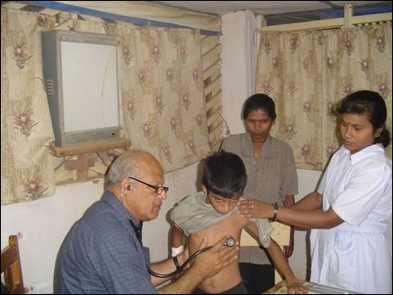 Dr Karunyan Arulanandam, a Paediatrician from Calfornia USA, examining a child while a local nurse helps out.