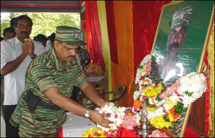 LTTE Special Commander Col. Balraj garlanding the photo of late LTTE commander Col. Ramanan