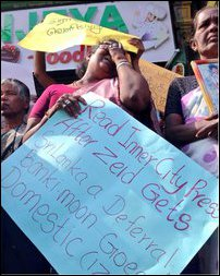 A protesting Tamil mother in Jaffna holding a slogan featuring the news headline from the Inner City